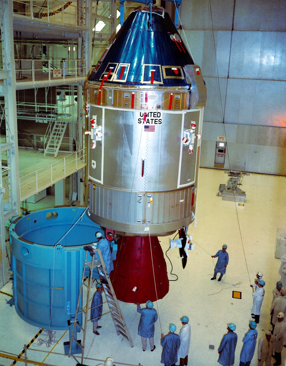 Apollo Spacecraft 107 Command and Service Modules (CSM), which was scheduled to be flown on the Apollo 11 lunar landing mission, shown being moved from the work stand for mating to Spacecraft Lunar Module Adapter (SLA) at the Kennedy Space Center's (KSC) Manned Spacecraft Operations Building. (Photo: NASA.)