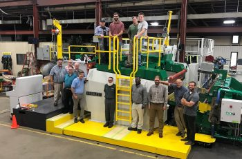 JW Aluminum and Hazelett employees standing with the new AS2000 twin-belt casting machine to be delivered to JW.
