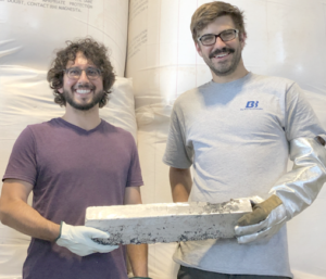 Figure 1. Boris Chubukov (right) and Aaron Palumbo (left), cofounders of Big Blue Technologies, hold the first magnesium ingot generated using the company's proprietary vacuum carbothermal reduction process.