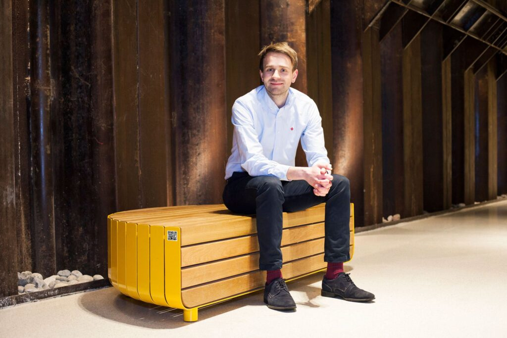 Jan Christian Vestre with one of his company's benches carrying a QR code for blockchain tracing. (Photo: Charlotte Sverdrup, Hydro)