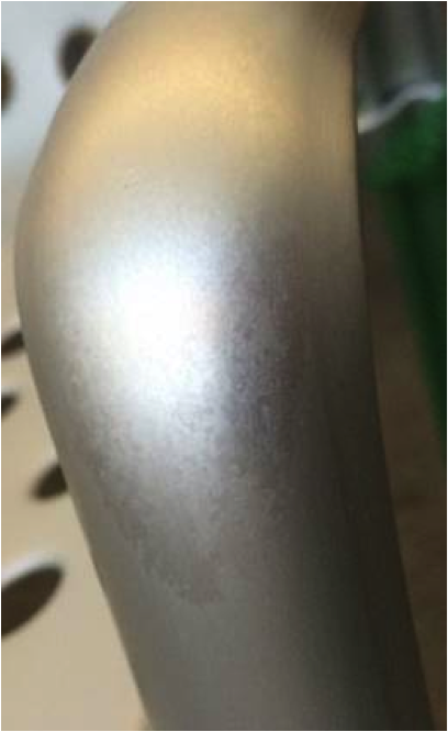 Figure 3. The bent arm of an aluminum chair with a grainy structure on the anodized surface.