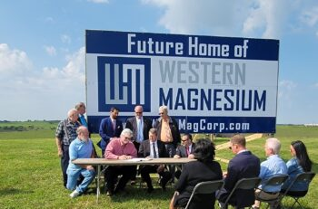 Western Magnesium - primary magnesium production - team members sit in front of a billboard, signing an agreement for the new location of the magnesium plant